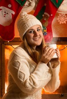 Closeup retrato de uma linda mulher com um suéter de lã bebendo chá na lareira
