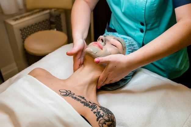 Closeup retrato de uma linda mulher com uma toalha na cabeça aplicando máscara facial
