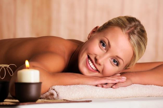 Closeup retrato de uma linda mulher sorridente, deitada em um salão de beleza