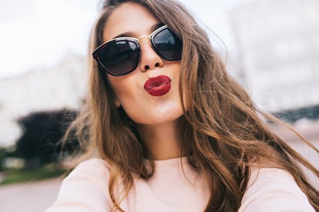 Closeup retrato de uma menina bonita em óculos de sol com penteado longo na cidade. ela dando um beijo com os lábios carnudos.