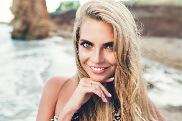 Closeup retrato de uma menina bonita loira com cabelos longos, posando na praia rochosa. ela está sorrindo para a câmera.