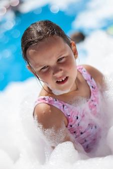 Closeup retrato de uma menina de cinco anos usando espuma em uma festa da espuma em um dia quente de verão na praia