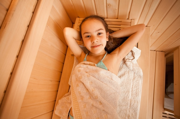 Closeup retrato de uma menina deitada na sauna