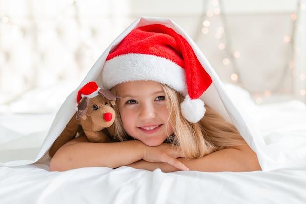 Closeup retrato de uma menina loira deitada na cama com um chapéu de papai noel e um cervo de brinquedo