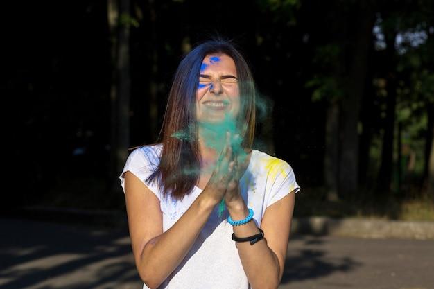 Closeup retrato de uma menina morena feliz posando com pó de holi verde explodindo no parque