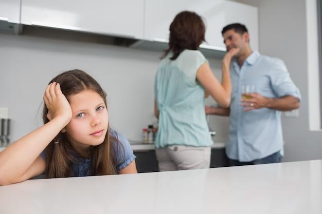 Closeup retrato de uma menina triste enquanto os pais se brigam