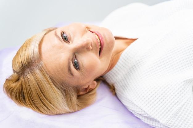 Closeup retrato de uma mulher adorável e alegre deitada no sofá em um escritório de esteticista