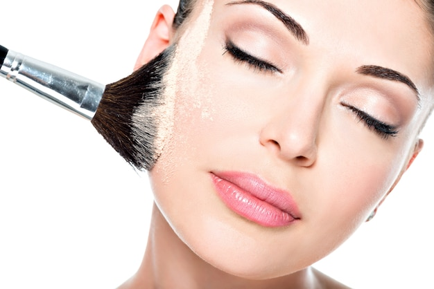 Closeup retrato de uma mulher aplicando base tonal cosmética seca no rosto usando o pincel de maquiagem.