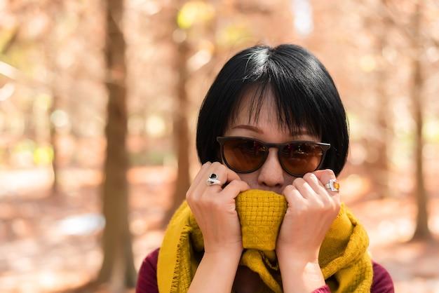 Closeup retrato de uma mulher asiática moderna madura na floresta