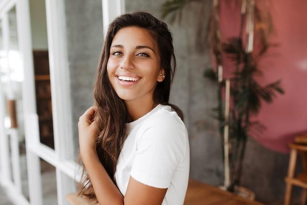 Closeup retrato de uma mulher bonita com uma camiseta branca, posando em uma sala cinza com móveis de madeira
