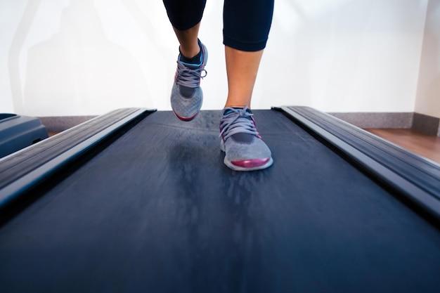 Closeup retrato de uma mulher com as pernas correndo na esteira
