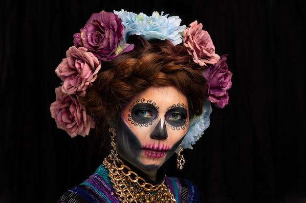 Closeup retrato de uma mulher com uma maquiagem de caveira de açúcar vestida com coroa de flores