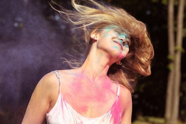 Closeup retrato de uma mulher loira atraente com cabelos esvoaçantes ao vento brincando com pó de holi Foto Premium