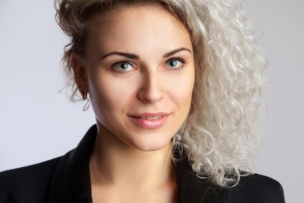 Closeup retrato de uma mulher loira bem encaracolada olhando para a câmera no estúdio