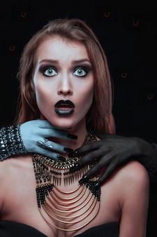 Closeup retrato de uma mulher muito gótica com mãos de vampiro em seu pescoço em fundo preto