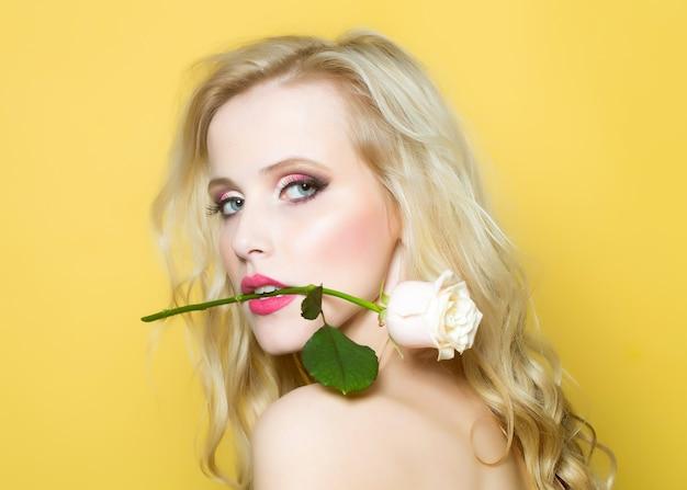 Closeup retrato de uma mulher sexy e apaixonada com ombro nu e maquiagem brilhante, segurando uma flor rosa na boca.