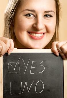 Closeup retrato de uma mulher sorridente segurando uma placa com duas respostas