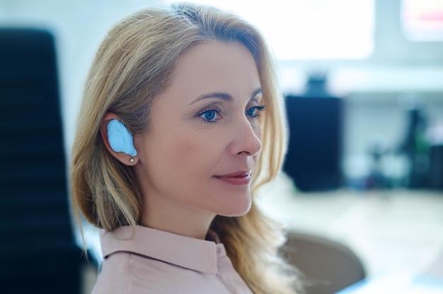 Closeup retrato de uma paciente calma e adorável com um dispositivo inserido no ouvido, sentada no consultório do otorrinolaringologista
