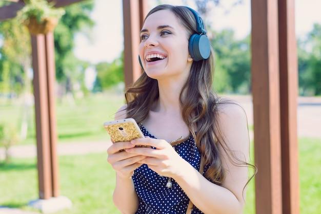 Closeup retrato de uma senhora muito otimista, engraçada, funky, vestindo um vestido retro pontilhado usando o telefone para encontrar a melodia favorita cantando, ouvindo uma aparência agradável