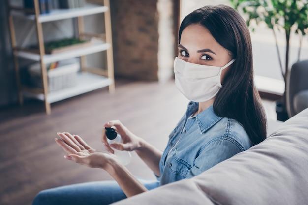 Closeup retrato dela bonita garota morena atraente sentada no divã, usando máscara de segurança, usando spray de desinfecção em apartamento moderno de casa industrial apartamento seguro lugar seguro dentro de casa