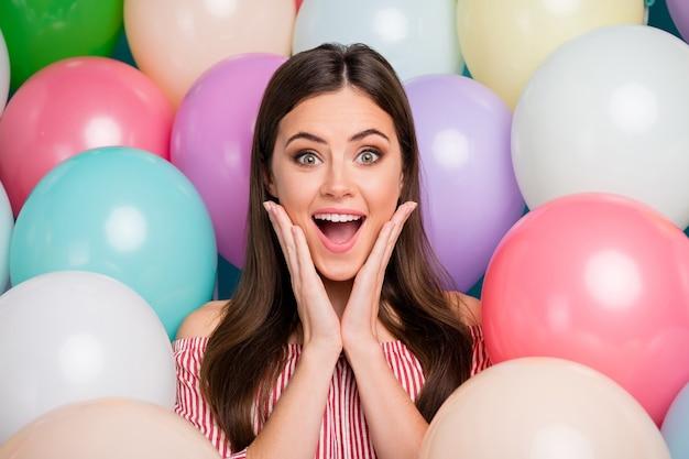 Closeup retrato dela ela agradável atraente adorável muito fofo espantada animada alegre alegre garota de cabelos compridos se divertindo entre bolas de ar coloridas curtindo um ótimo tempo