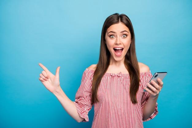 Closeup retrato dela, ela é agradável, atraente, adorável, muito louca, alegre, alegre, menina, usando o celular, demonstrando o novo anúncio de novidade isolado sobre fundo de cor azul vibrante brilho vívido