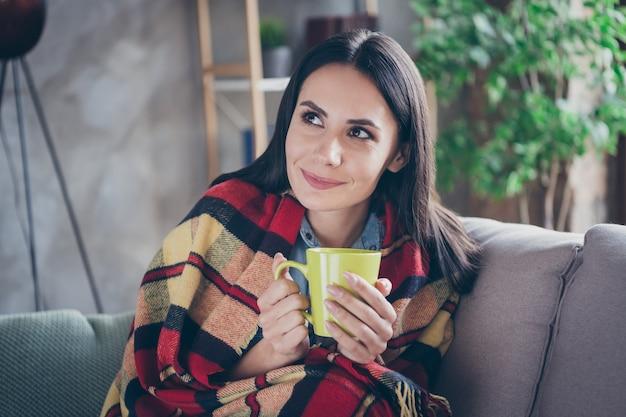Closeup retrato dela, ela é simpática, atraente, linda linda garota morena, sentada no véu coberto de divã, bebendo chá verde quente de ervas, e passando o tempo livre em um apartamento moderno em casa industrial de tijolos