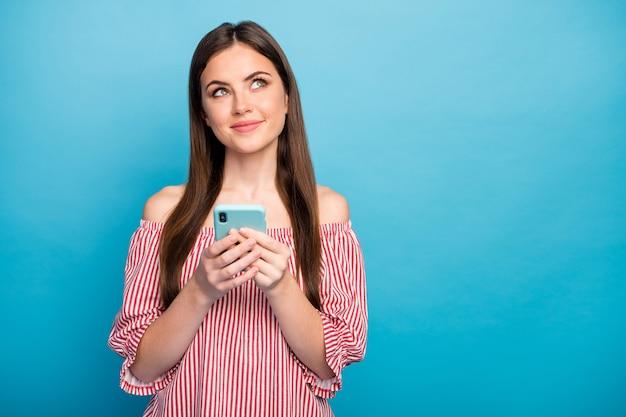 Closeup retrato dela, ela parecendo atraente, adorável, alegre, sonhadora, menina, usando o novo aplicativo de dispositivo da loja online, isolado sobre fundo de cor azul vibrante brilhante brilho vívido