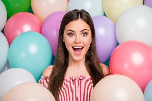 Closeup retrato dela, linda, atraente, adorável, alegre, alegre, adolescente, de cabelos compridos, se divertindo entre bolas de ar coloridas, curtindo o dia festivo, bom humor