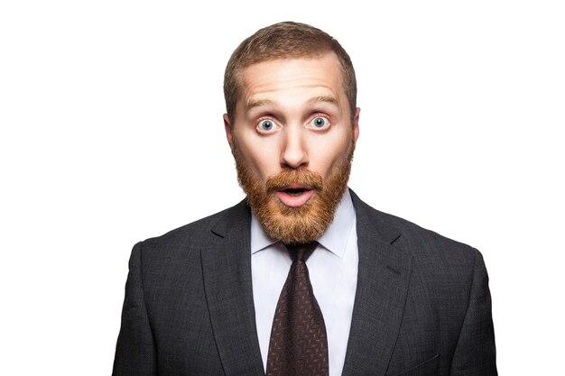 Closeup retrato do empresário bonito chocado com barba facial em terno preto em pé e olhando para a câmera com olhos grandes e boca aberta. estúdio interno tiro isolado no fundo branco.