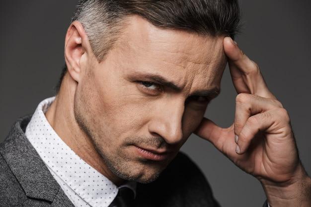 Closeup retrato do homem caucasiano atraente com roupa formal e tocar a testa com o dedo enquanto pensava ou lembrando, isolado sobre a parede cinza
