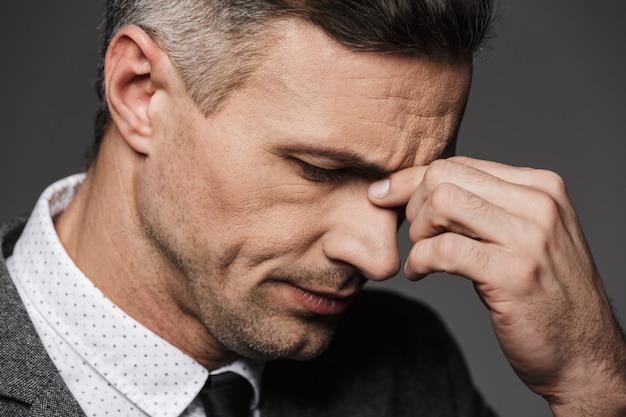 Closeup retrato do homem caucasiano exausto com roupa formal, fechando os olhos e tocando a ponte do nariz, isolada sobre a parede cinza