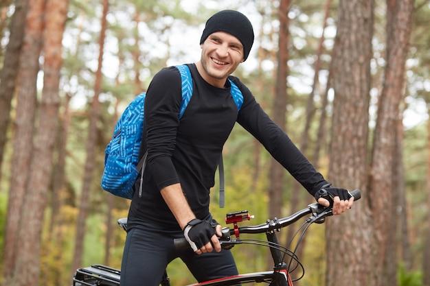 Closeup retrato do homem ciclista sorridente, andar de bicicleta de montanha na trilha no parque ou floresta, desfrutando de ar fresco e natureza, veste sportwear preto, boné e mochila azul. conceito de estilo de vida saudável