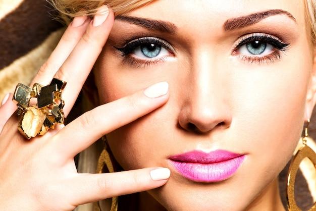 Closeup retrato do lindo rosto de uma mulher sexy com maquiagem fashion e anel de ouro no dedo