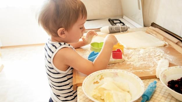 Closeup retrato do menino fofo da criança de 3 anos de pé na cozinha e cozinhar massa. criança assando e fazendo café da manhã