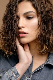 Closeup retrato do modelo de moda beleza com pele limpa e cabelos cacheados em jaqueta jeans jeans na parede bege, cabelo molhado do modelo