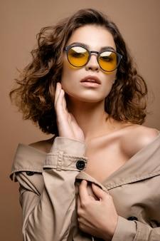 Closeup retrato do modelo de moda beleza com pele limpa e cabelos encaracolados na capa de biege esticar, modelo de óculos da moda, ombros nus