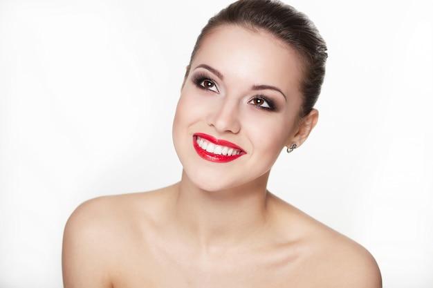Closeup retrato do modelo sexy caucasiano jovem sorridente com lábios vermelhos de glamour, maquiagem brilhante, maquiagem de seta dos olhos, pele de pureza. pele limpa perfeita. dentes brancos