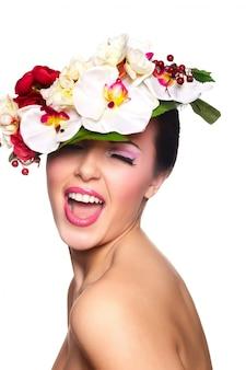 Closeup retrato do modelo sexy caucasiano morena sorridente sexy jovem com os lábios de glamour, maquiagem brilhante. com flores coloridas na cabeça