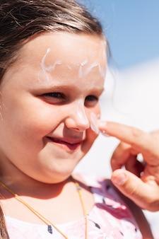 Closeup retrato do pai aplicando protetor solar no rosto e nariz de suas filhas, férias em família e viagens ...