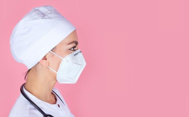 Closeup retrato do perfil de uma jovem médica com uma máscara protetora médica em uma parede rosa com um espaço para texto