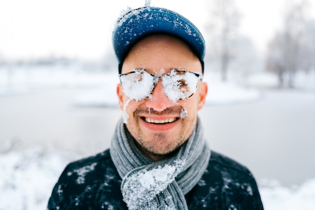 Closeup retrato do rosto masculino sorridente, coberto de neve em um dia frio de inverno.