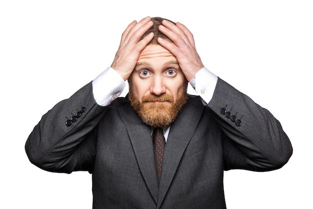 Closeup retrato do triste empresário bonito com barba facial em terno preto em pé segurando sua cabeça e olhando para a câmera com tristeza sem esperança. estúdio interno tiro isolado no fundo branco.