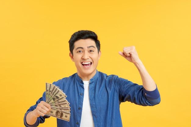 Closeup retrato, feliz, animado homem idoso sortudo sênior bem sucedido segurando dinheiro notas de dólar na mão isolado de fundo amarelo. sentimento de expressão facial de emoção positiva. economia de recompensa financeira