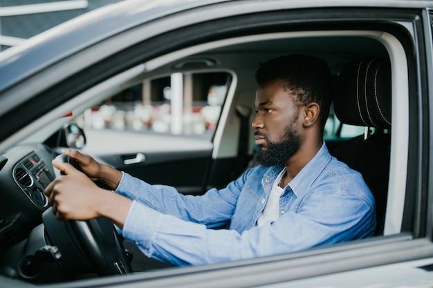 Closeup retrato feliz e sorridente jovem africano sentado em seu carro novo animado, pronto para a viagem