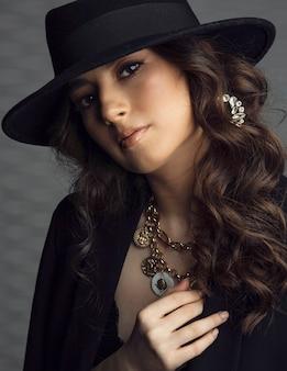 Closeup retrato frontal de uma jovem esplêndida mulher morena de jaqueta preta e chapéu com maquiagem, cabelo encaracolado, sobre fundo cinza.