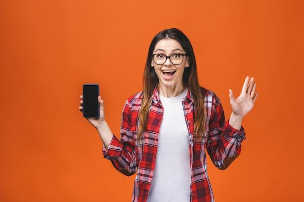 Closeup retrato headshot mulher usando telefone celular isolado sobre o fundo da parede laranja