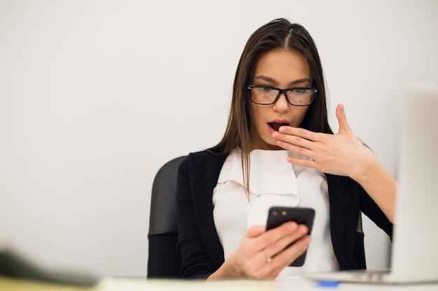 Closeup retrato jovem, chocado mulher de negócios, olhando para o celular vendo mensagem de texto ruim, e-mail, escritório isolado dentro de casa. emoções negativas, expressões faciais