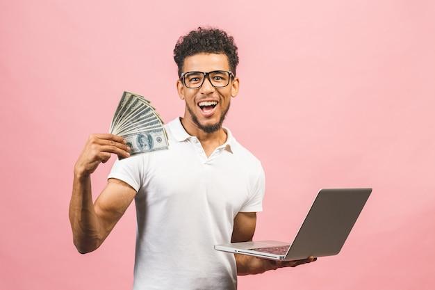 Closeup retrato, jovem empresário de sucesso americano africano ganhando dinheiro com a internet, segurando dinheiro na mão, laptop em outra