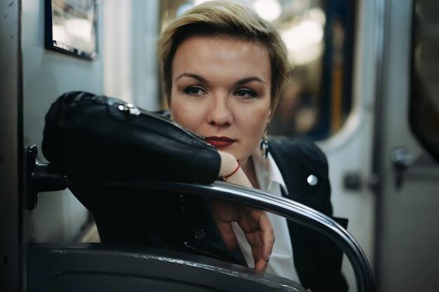 Closeup retrato jovem mulher caucasiana vestindo jaqueta de couro, sentada no carro do metrô